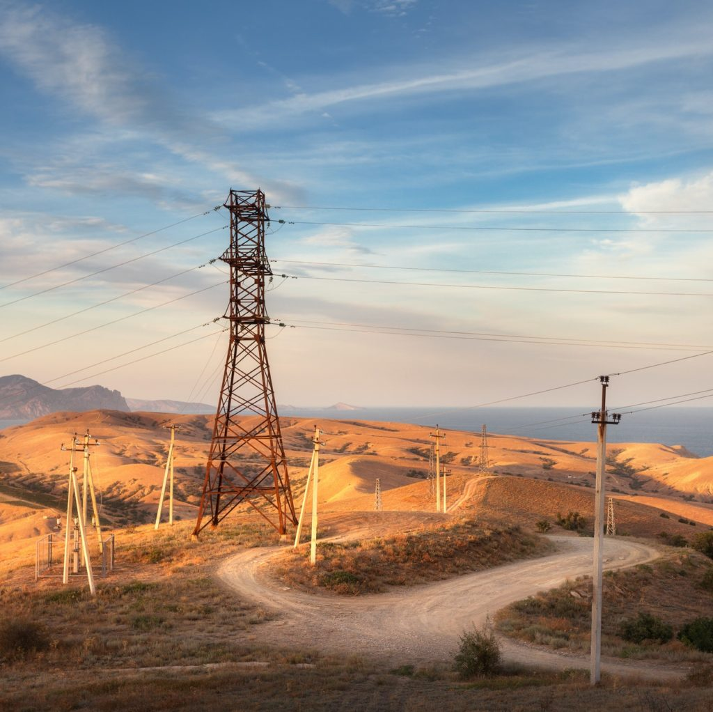 High voltage tower in mountains at sunset. Electricity pylon system