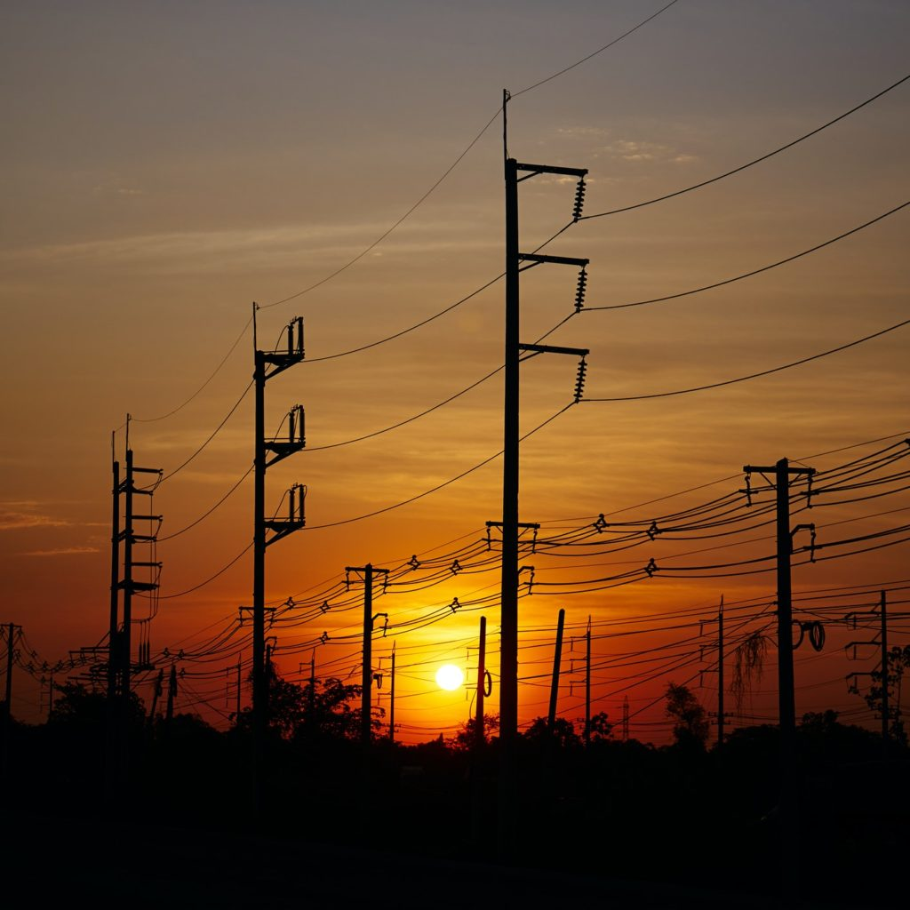 The electric poles and electric lines with a sky of sunset